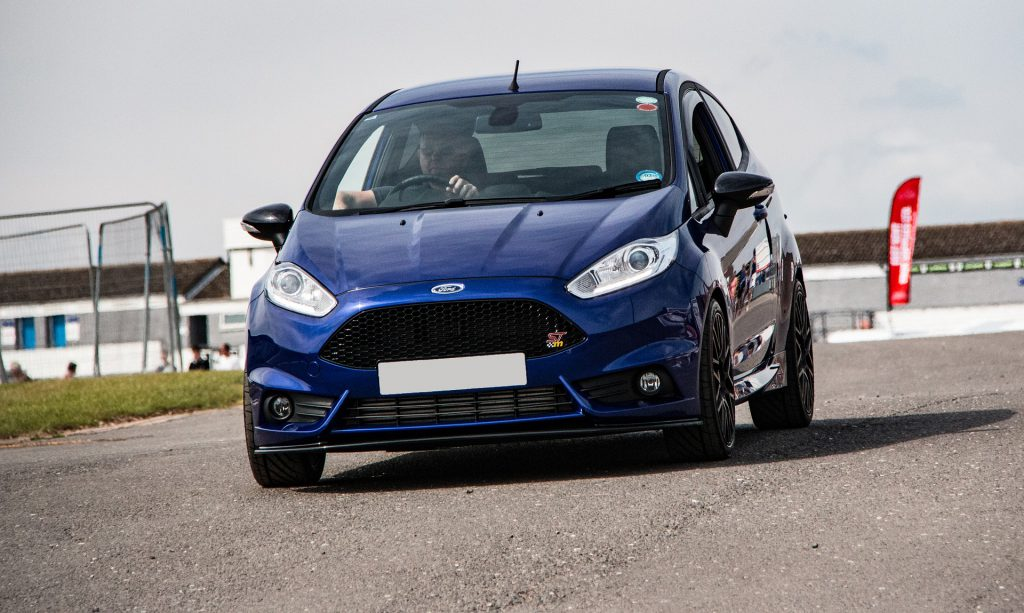 Man driving his Ford Fiesta after its fresh windscreen replacement.
