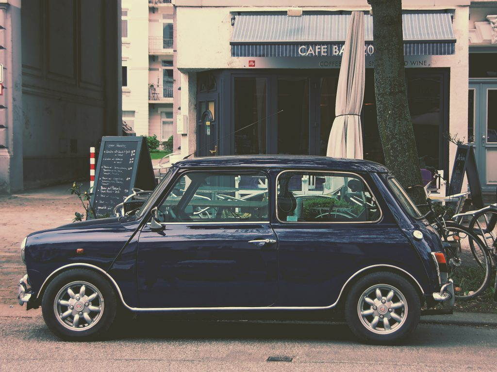 A vintage style Mini Cooper parked outside.