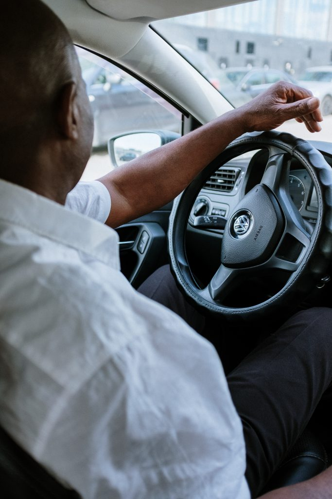 Interior of a Volkswagen with driving resting on wheel