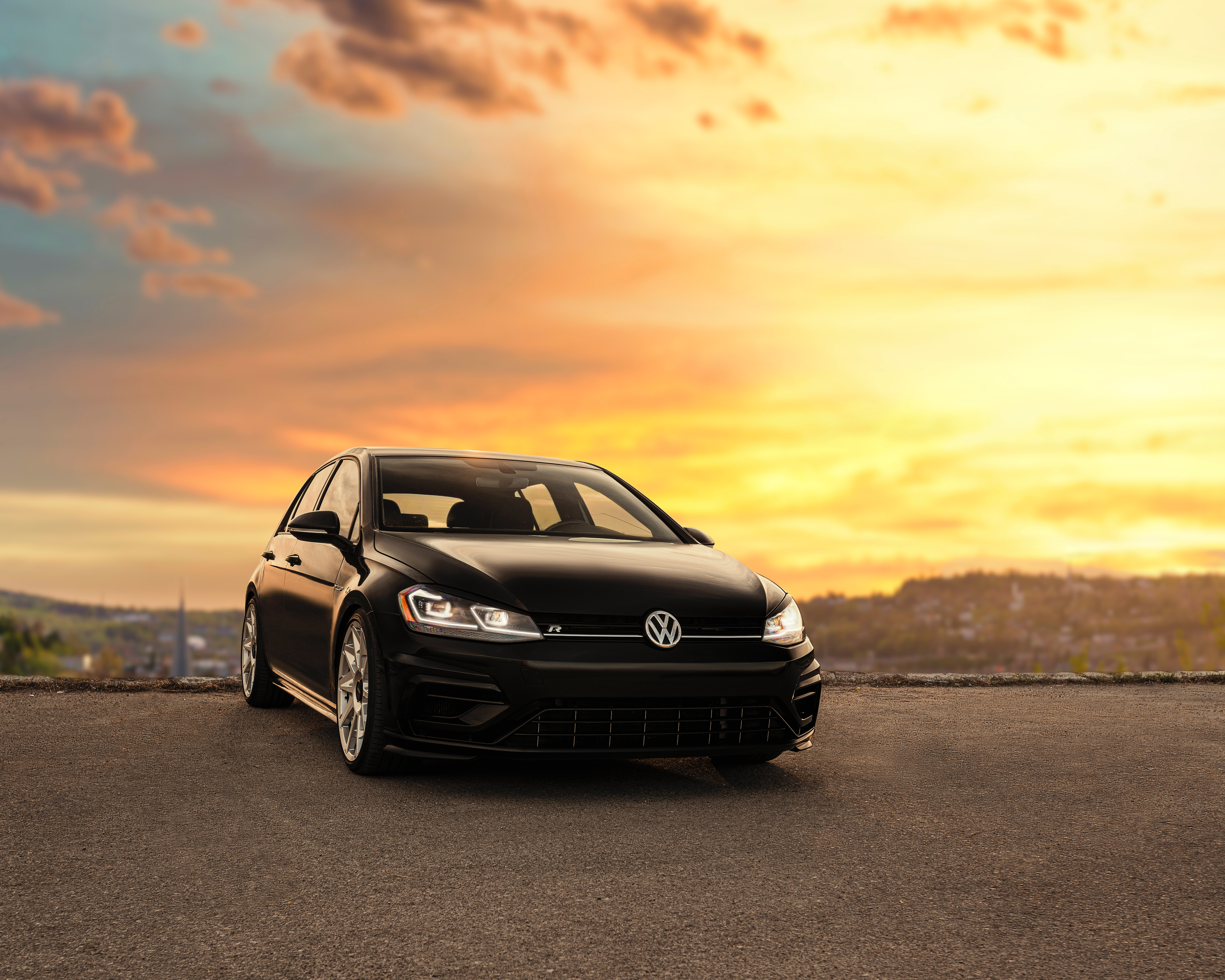 A beautiful black Volkswagen Golf with a sunset background
