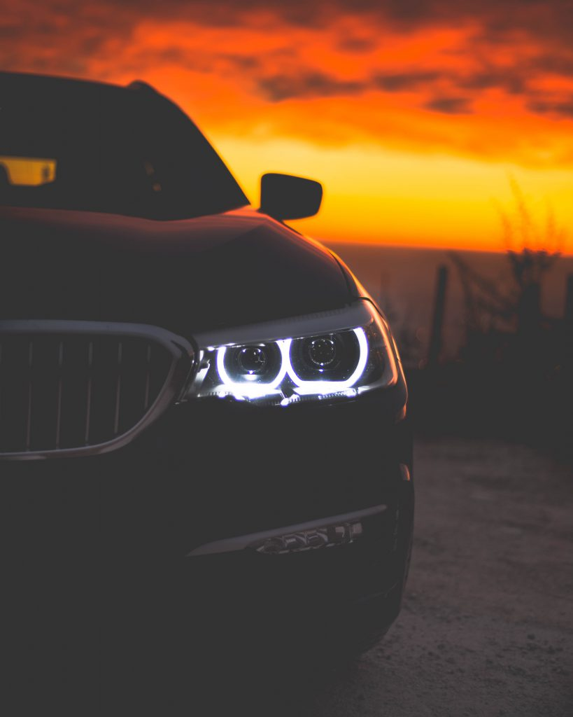 Black BMW 3 Series by a glowing sunset