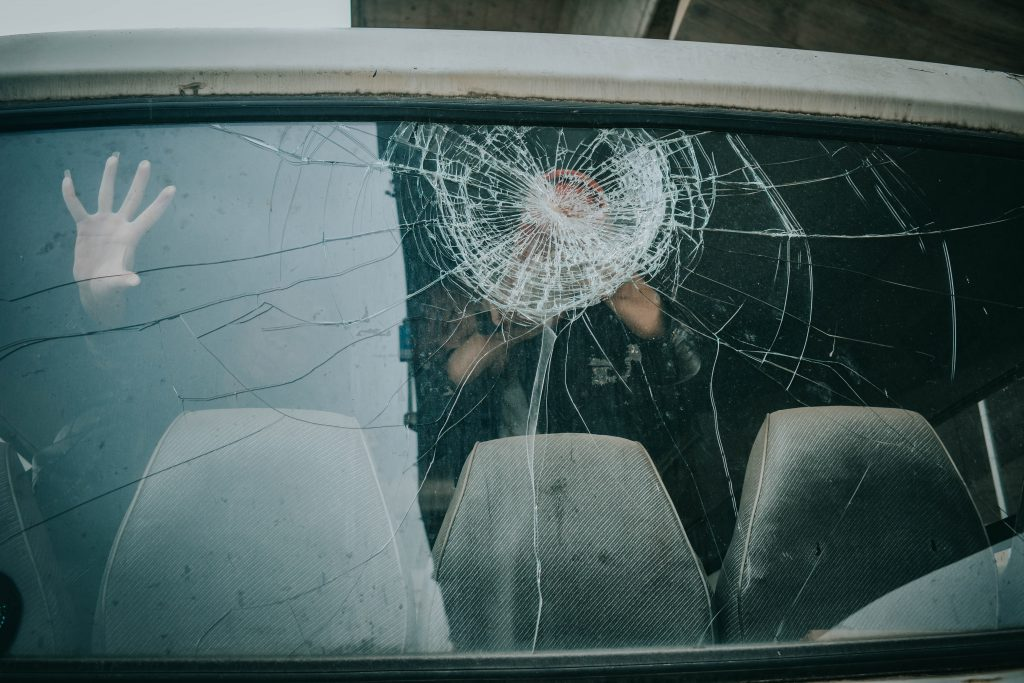 Cracked rear windscreen, with people trying to break through and escape