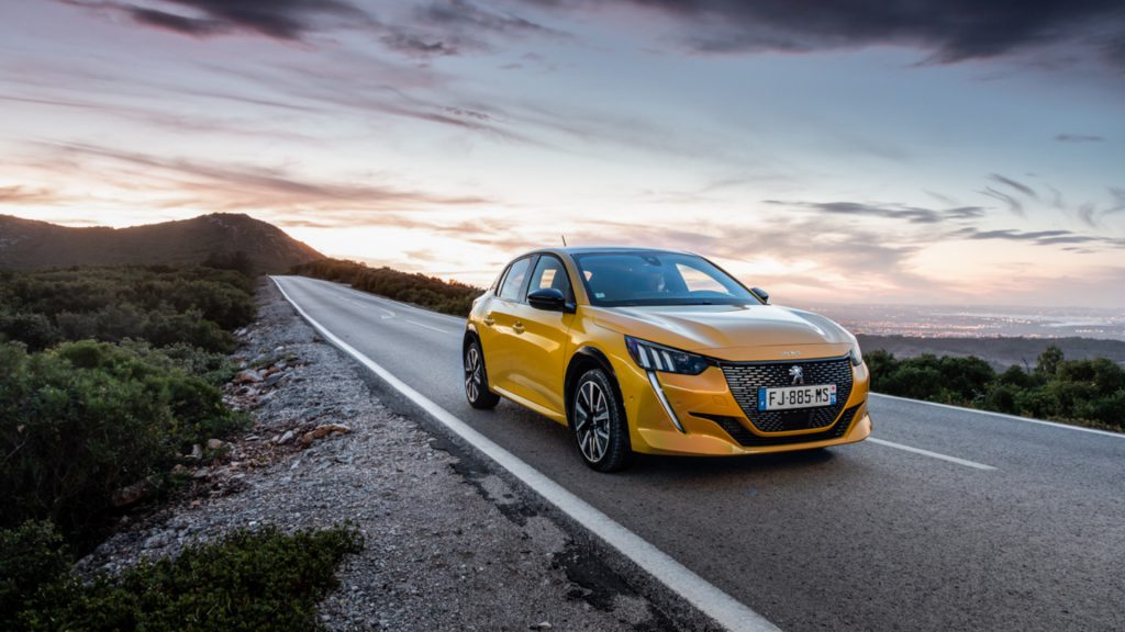Yellow Peugeot 208 driving along the road