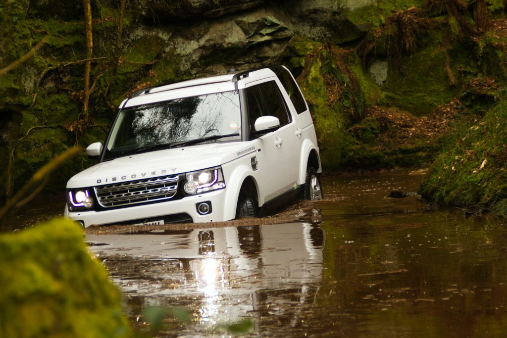White Land Rover Discovery driving through water and the wild