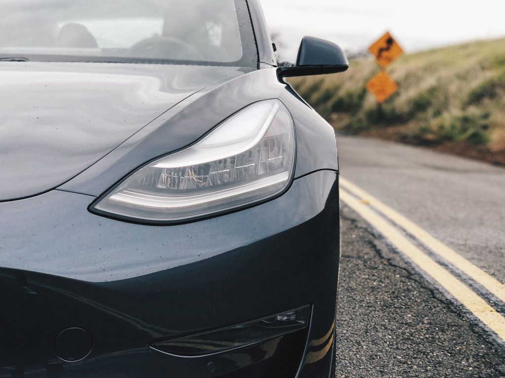 Grey  Tesla Model 3  on the road with its car glass being repaired.