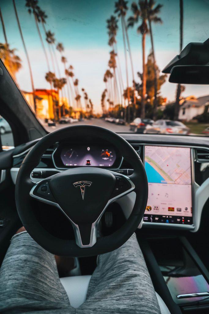 Interior shot with Tesla emblem on steering wheel